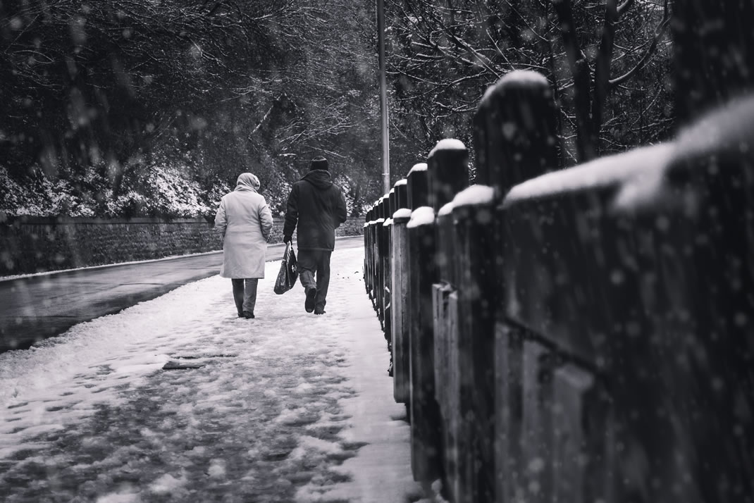 Two seniors walking on a snowy road