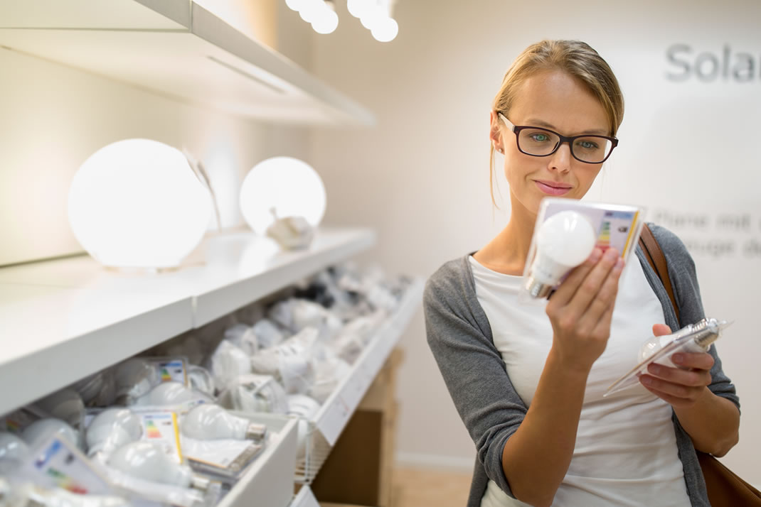 Young woman considering LED light bulbs in a store